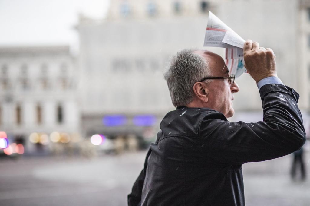 Man on the street with a brochureმამაკაცი კუჩაში ბროშურით