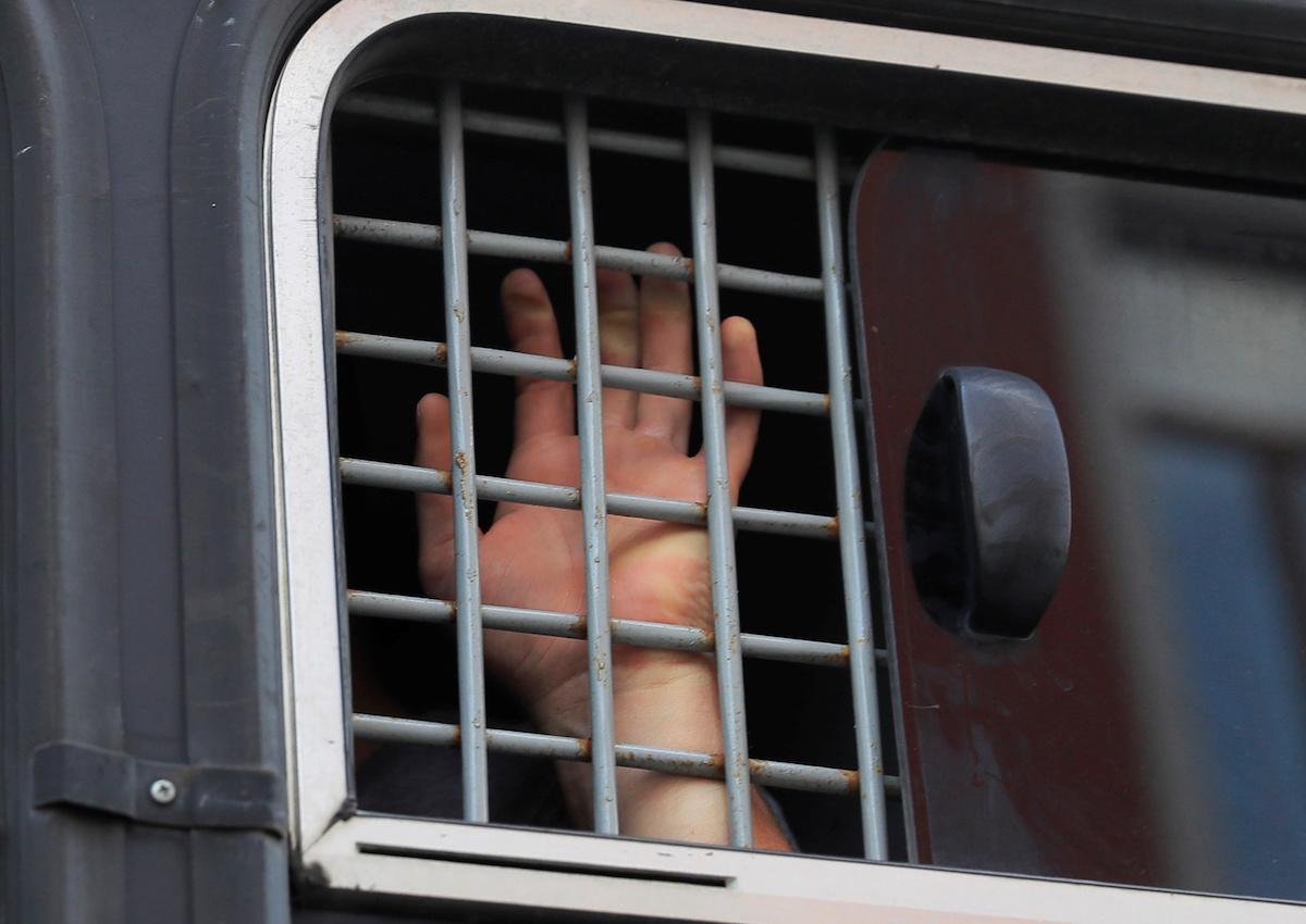 Рука задержанного протестующего  в полицейском автобусе