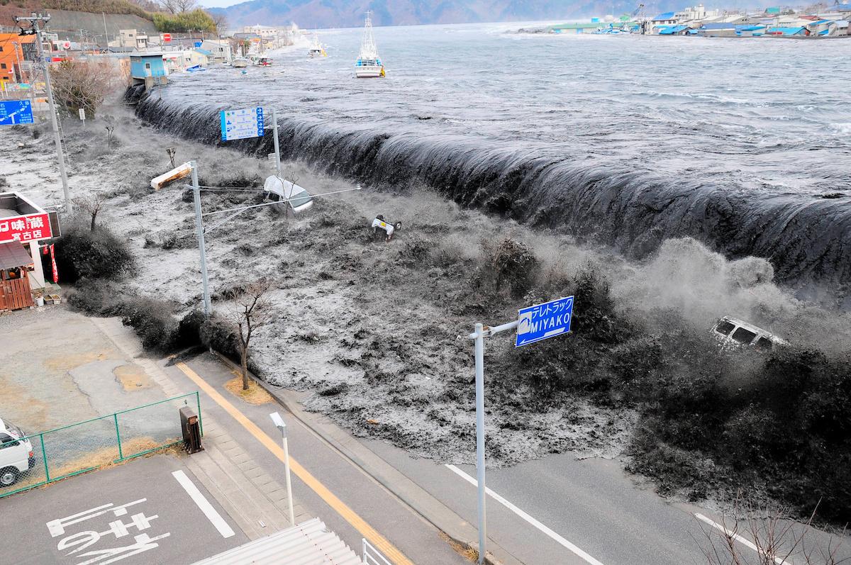 Волна от цунами обрушивается на город Мияко на северо-востоке Японии после землетрясения силой 8,9 балла. 11 марта 2011 года.