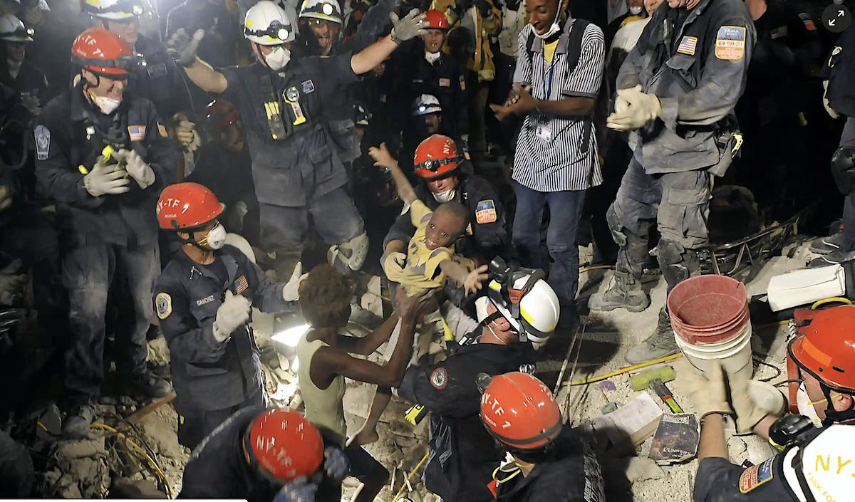 Спасатели вытащили из-под завалов живого ребенка. 14 января 2010. Фото Reuters