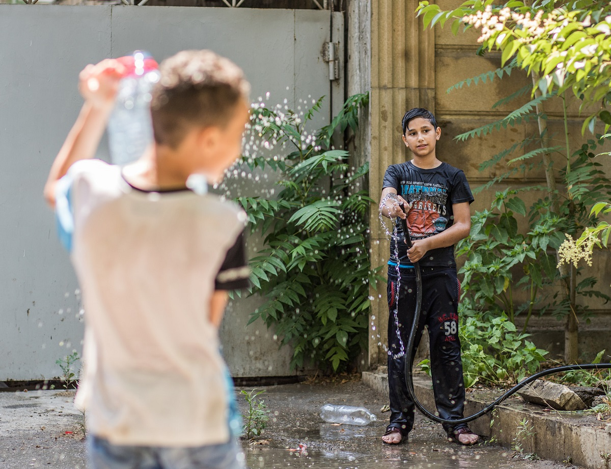 The children are playing with water on the streets of poor district in Baku