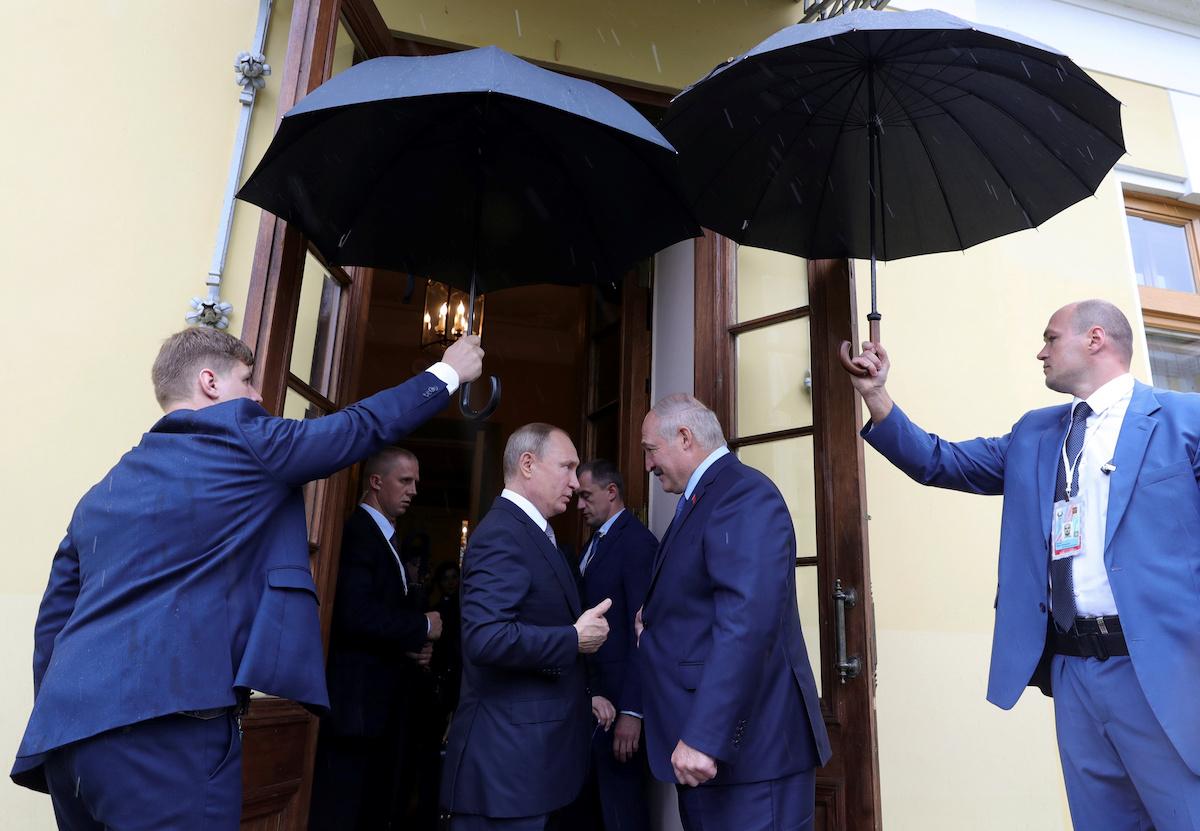 ვლადიმერ პუტინი ალექსნადრე ლუკაშენკო საქნტ-პეტერბურგის შეხვედრაზე. თანაშემწეები ქოლგებით იცავენ წვიმისგან