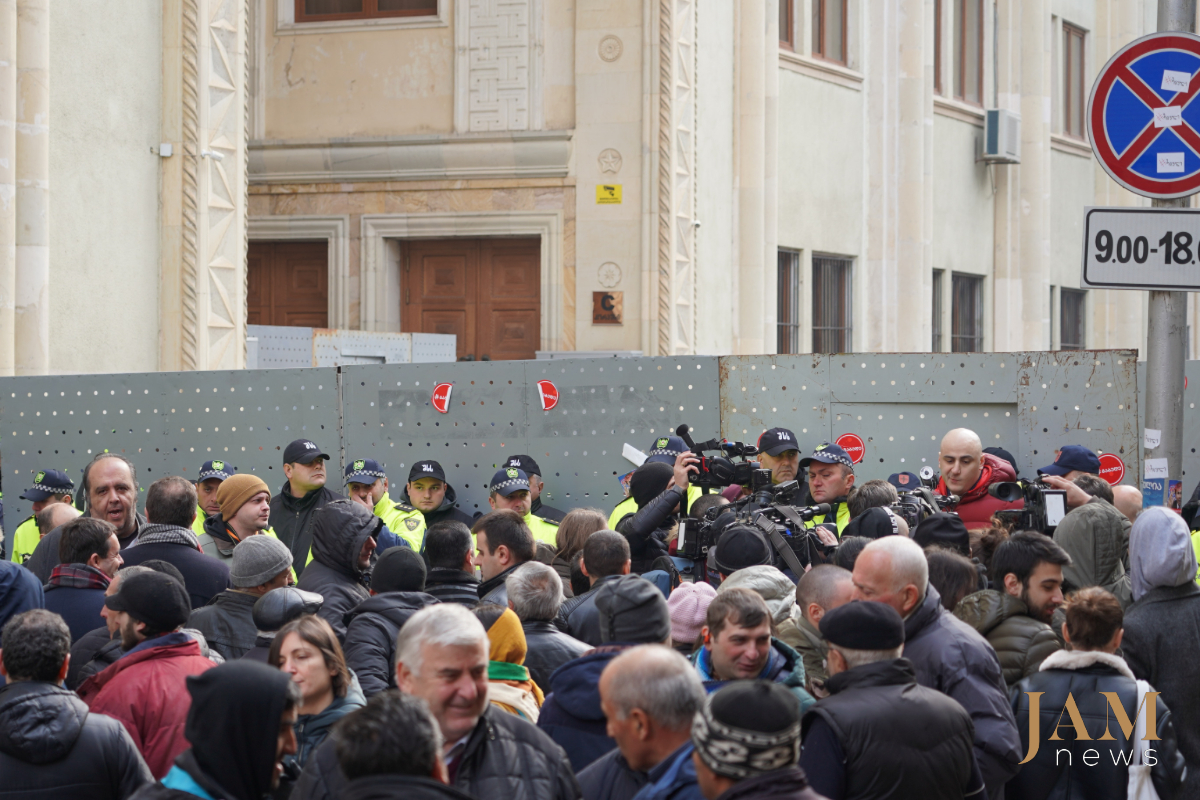 Митингующие и полицейские возле здания парламента აქციის მონაწილეები და პოლიციელები პარლამენტის რკინის მესერთან