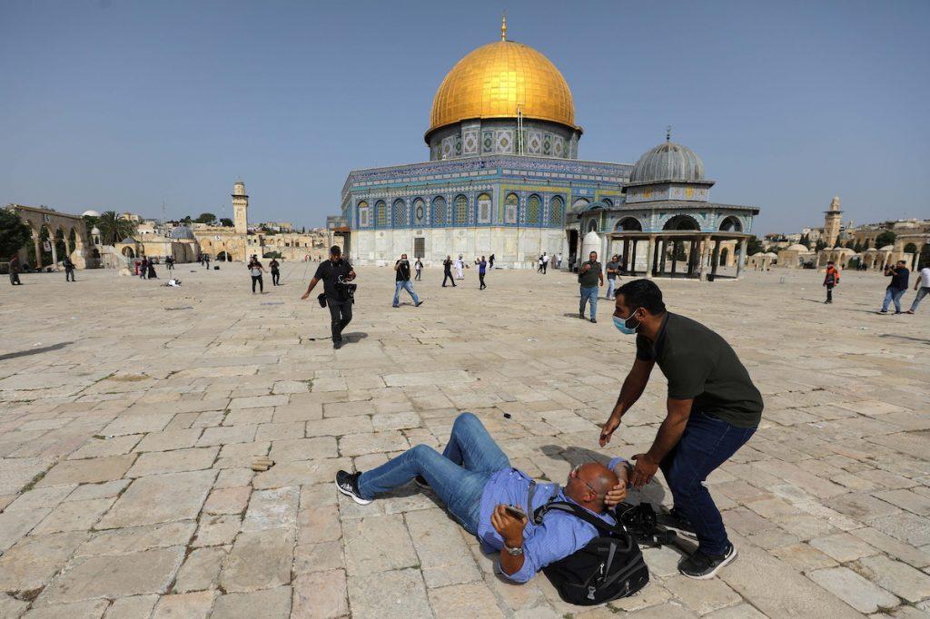 Оператора сбили с ног во время столкновений палестинцев с израильской полицией на территории мечети Аль-Акса в Иерусалиме, ему помогает встать один из участников протеста. 10 мая, 2021. REUTERS/Ammar Awad Что происходит в израильско-палестинском конфликте