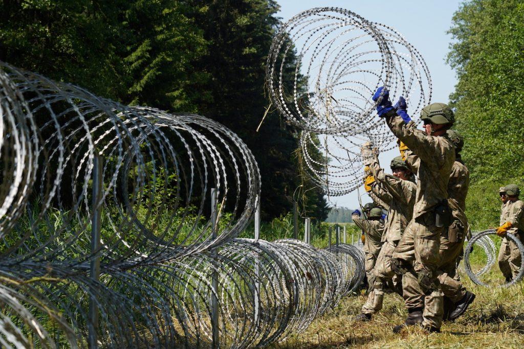 Солдаты литовской армии устанавливают колючую проволоку на границе с Беларусью в Друскининкае, Литва, 9 июля 2021 года. REUTERS/Janis Laizans