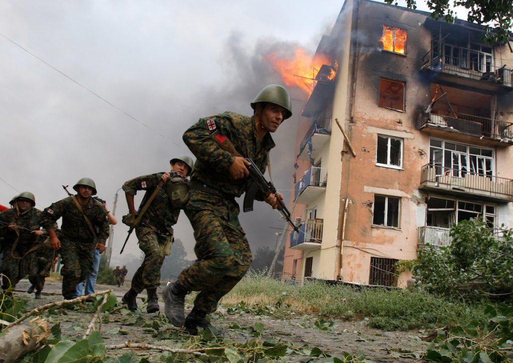 ქართველი ჯარისკაცები ქალაქ გორში, რუსული დაბომბვის შემდეგ დამწვარ შენობასთან. 9 აგვისტო, 2008 წ. REUTERS / Глеб Гаранич
