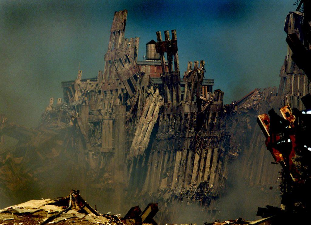 Дым продолжает подниматься от останков Башен-близнецы Торгового центра в Нью-Йорке. Фото снято 16 сентября 2001 года.  REUTERS/Shaun Best