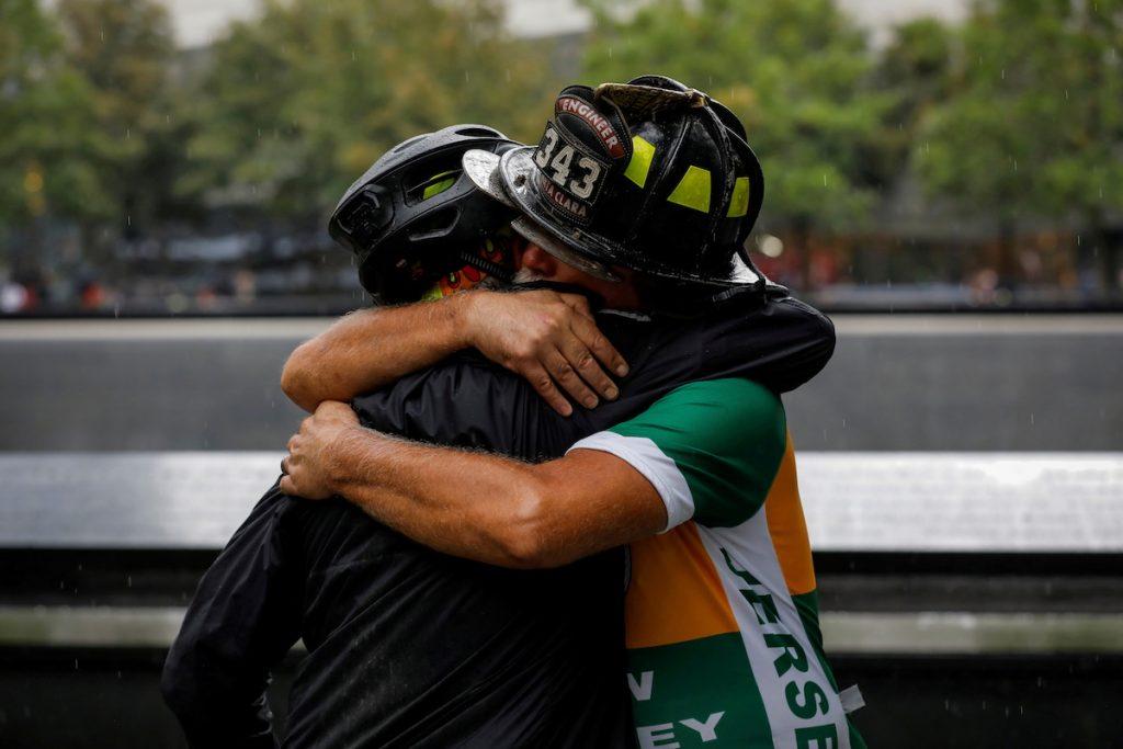 Пожарный на пенсии Даррелл Сейлз из Санта-Клары обнимает другого участника велопробега, организованного в ознаменование 20-й годовщины терактов в Нью-Йорке 11 сентября. Фото снято у Мемориала 9/11 9 сентября, 2021. REUTERS/Andrew Kelly