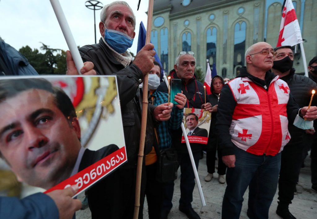 Люди протестуют перед зданием парламента в Тбилиси, требуя освобождения бывшего президента Грузии Михаила Саакашвили. 10 октября 2021 г. REUTERS / Ираклий Геденидзе